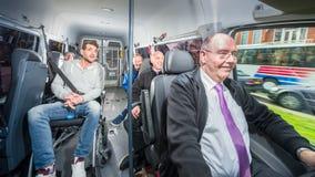 Grupp människor som reser i en minivan med en busdriver och en di Arkivfoton