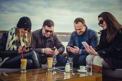 Grupp människor som ser en mobiltelefon och skratta Royaltyfria Foton