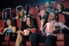 Grupp människor som skrattar på filmbiografen