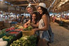 Grupp människor som tillsammans väljer grönsaker på för köpprodukter för marknad som lyckliga le unga turister shoppar nytt exoti fotografering för bildbyråer