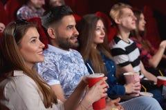 Grupp människor som tycker om film på bion Royaltyfria Bilder