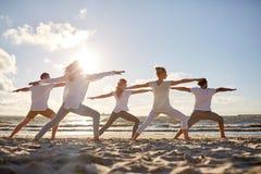 Grupp människordanandeyoga övar på stranden royaltyfri bild