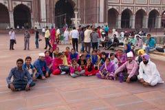 Grupp människorsammanträde på Jama Masjid i Delhi, Indien royaltyfri bild