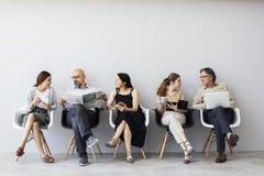Grupp människorsammanträde på stolar arkivbild