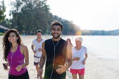 Grupp människorspring, unga sportlöpare som joggar på stranden som utarbetar le lyckliga färdiga manliga och kvinnliga Joggers arkivbilder