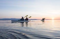 Grupp människorvänhav som tillsammans kayaking på solnedgången i härlig natur Aktiva utomhus- affärsföretagsportar royaltyfri foto