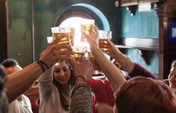 Grupp m?nniskor som firar i en bar som dricker ?l royaltyfri fotografi