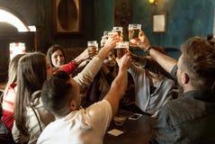 Grupp m?nniskor som firar i en bar som dricker ?l arkivfoton