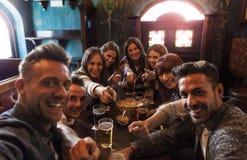Grupp m?nniskor som firar i en bar som dricker ?l arkivfoto