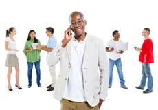 Grupp människor som använder kommunikationsapparaten Arkivbild