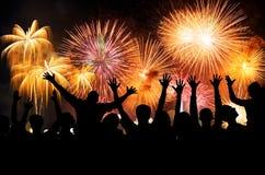 Grupp människor som tycker om spektakulära fyrverkerier, visar i en karneval eller semestrar Royaltyfri Fotografi