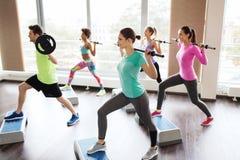 Grupp människor som övar med skivstången i idrottshall Royaltyfri Bild