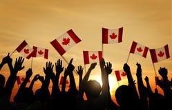 Grupp människor som vinkar den kanadensiska flaggan Arkivfoton