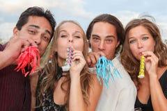 Grupp som blåser horn som firar nytt år fotografering för bildbyråer