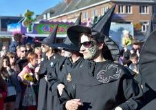 Grupp som föreställer häxor i svartdräkter i passage under årlig karneval Royaltyfria Foton