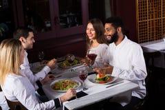 Grupp som har matställen i restauran Royaltyfria Bilder