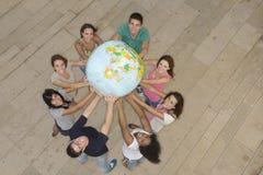 Grupp som rymmer jordjordklotet som visar Afrika Royaltyfri Fotografi