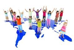 Gruppbarnhänder up stående världskartabegrepp Arkivbild