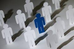 Gruppe ähnliche Papierpuppen mit einem blauen  Lizenzfreies Stockfoto