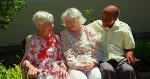 Gruppe ältere Freunde der aktiven Mischrasse, die auf einander im Garten des Pflegeheims einwirken stock video