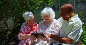 Gruppe ältere Freunde der aktiven Mischrasse, die digitale Tablette im Garten des Pflegeheims 4k verwenden stock footage
