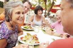Gruppe ältere Freunde, die Mahlzeit Restaurant im im Freien genießen stockbild