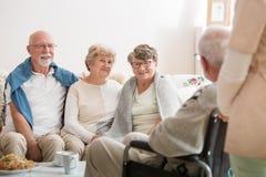 Gruppe ältere Freunde, die zusammen im allgemeinen Wohnzimmer des Pflegeheims sitzen stockfoto