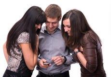Gruppe überraschte Leute, die einen Handy betrachten Lizenzfreie Stockfotos