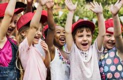 Gruppe angehobenen Glücklächelns der Kinderschulfreunde des Hand lernen Lizenzfreies Stockfoto