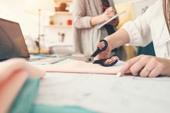 Gruppe Arbeit mit zwei Näherinen in nähendem Studio 3d getrennt auf Weiß Bewirken Sie seitlichen 50mm Nikkor Team der jungen Frau lizenzfreies stockfoto