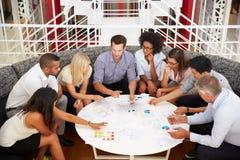 Gruppe Arbeitskollegen, die Sitzung in einer Bürolobby haben lizenzfreies stockbild