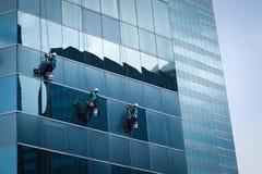 Gruppe Arbeitskräfte, die Fensterservice am hohen Aufstiegsgebäude säubern Lizenzfreie Stockfotografie