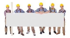 Gruppe Arbeitskräfte mit leerem Plakat Lizenzfreie Stockfotografie