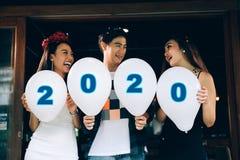 Gruppe asiatische junge Leute, die Ballonzahlen 2020, Konzept des neuen Jahres der Feier halten stockbilder