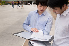 Gruppe asiatische Leute des Geschäfts, die über Bericht stehen und sprechen Lizenzfreie Stockfotografie