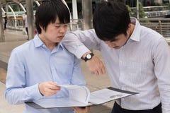 Gruppe asiatische Leute des Geschäfts, die über Bericht stehen und sprechen stockfotos