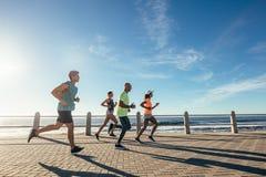 Gruppe Athleten, die auf Ozeanfront laufen lizenzfreie stockfotos