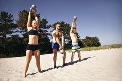 Gruppe Athleten, die mit Kesselglocke auf Strand ausarbeiten lizenzfreie stockbilder