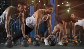 Gruppe athletische M?nner, die Training dr?ckt, Ups in Turnhalle lizenzfreie stockfotos