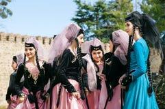 Gruppe attraktive junge Mädchen in den schönen Kleidern, die am Ereignis des Stadtfestivals sich treffen Stockfoto