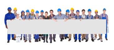 Gruppe Bauarbeiter mit Plakat Stockbild