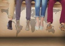 Gruppe Beine der Leute, die auf hölzerner Planke vor Weltkarte sitzen Stockfotografie