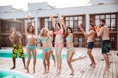 Gruppe beste Freunde, die Spaß am Swimmingpool haben Stockbild