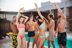 Gruppe beste Freunde, die Spaßtanzen am Swimmingpool haben Stockfotografie