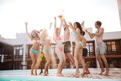 Gruppe beste Freunde, die Spaßtanzen am Swimmingpool haben Stockfotos