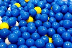 Gruppe blaue, gelbe und weiße Plastikbälle Stockfoto