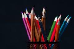 Gruppe bunte geschärfte Bleistifte auf Schwarzem Stockbilder