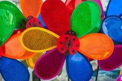 Gruppe bunte Plastikblumen mit Marienkäfern Lizenzfreie Stockbilder