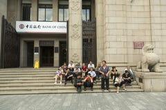 Gruppe chinesische Touristen, die Pause an der Treppe des Bank von China-Eingangs machen Lizenzfreie Stockfotos