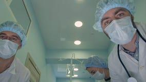 Gruppe Chirurgen, die unten auf dem Weg Patienten zum Operationsraum betrachten Stockfoto